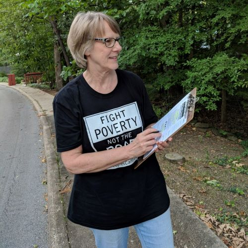 Woman holding clipboard with a Fight Poverty T-shirt